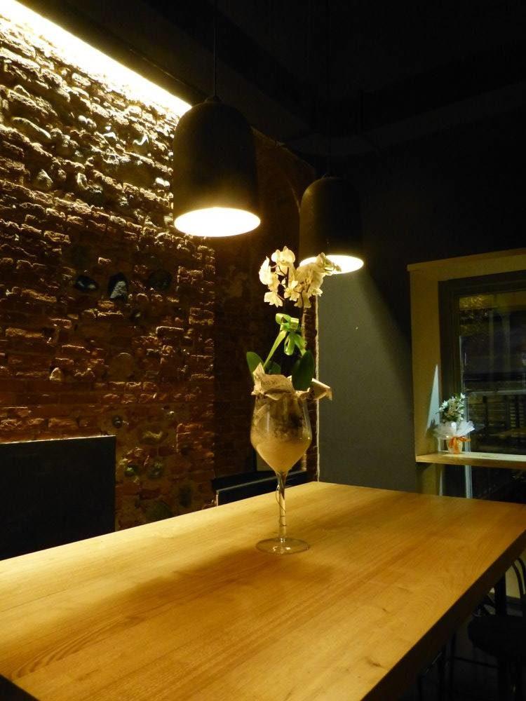 tavolo grande in legno e muro in mattoni a vista del d.one di san salvario torino