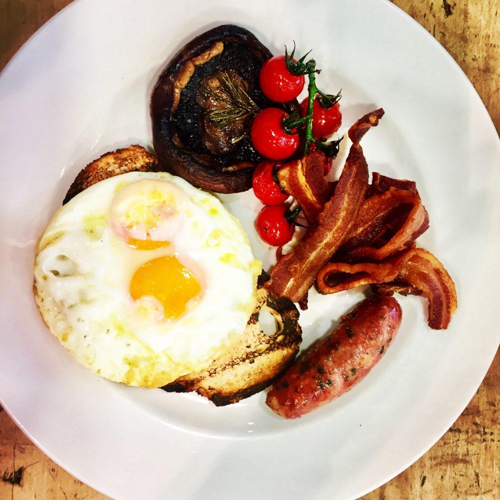 brunch con uova, bacon, salsiccia e funghi