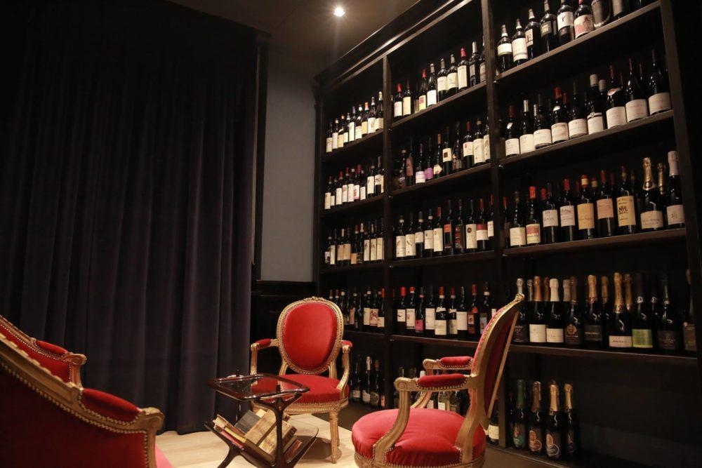 salottino con poltroncine rosse e scaffali con vini e champagne