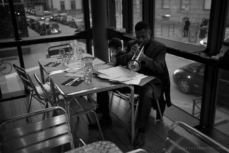 uomo che suona la tromba seduto ad un tavolino