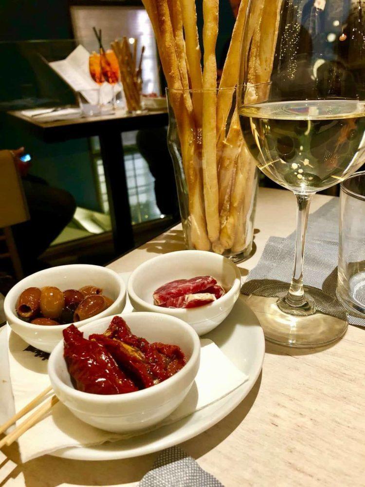 aperitivo con calice di vino bianco, ppomodori secchi olive salame e grissini