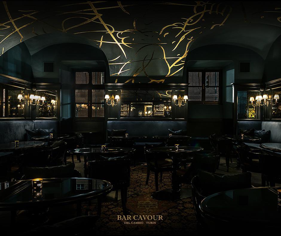 interno del bar cavour di torino con sedie e tavoli neri e atmosfera intima e sofisticata