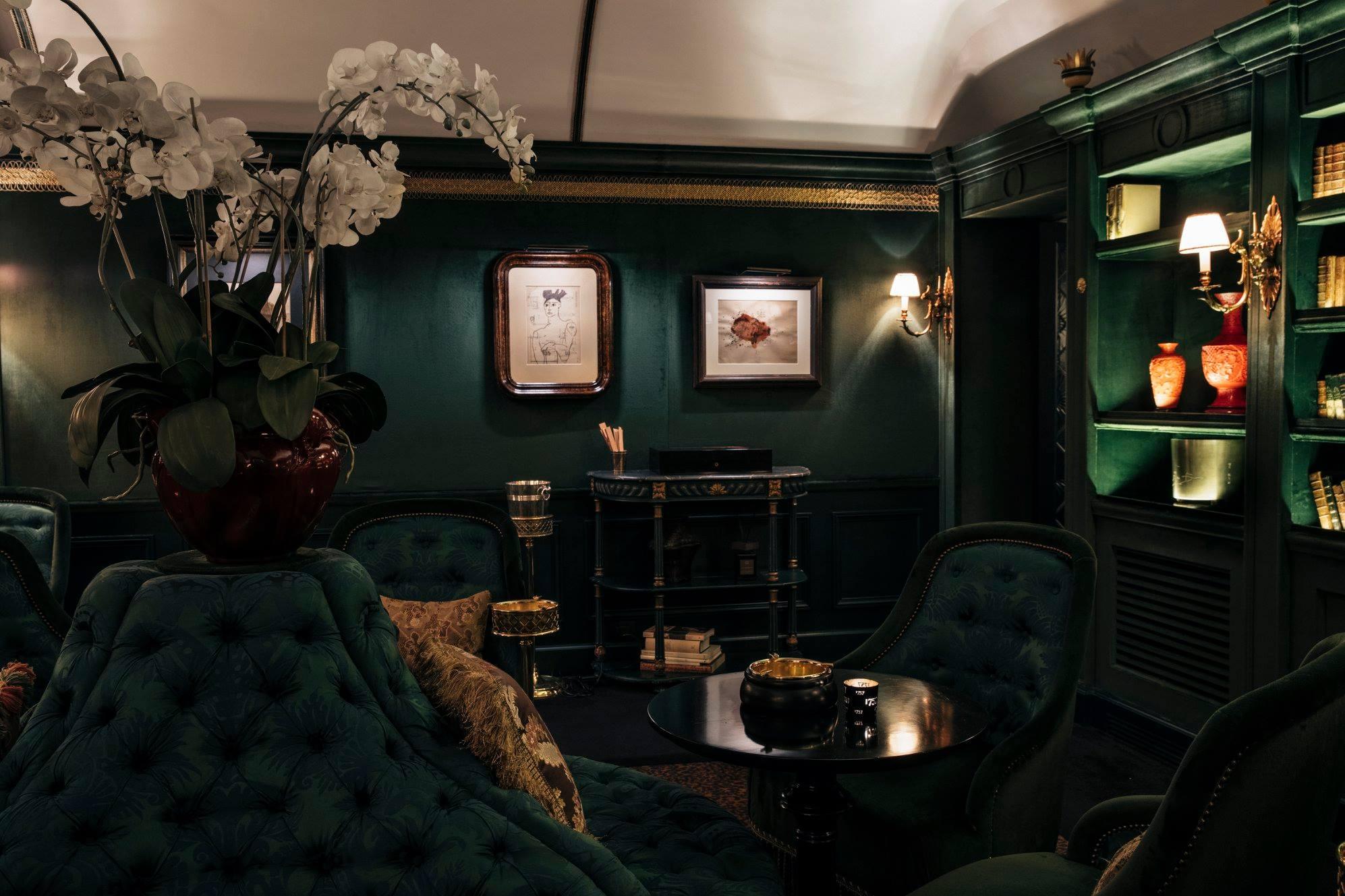 stanza con poltrone e pareti verdi, cuscini damascati