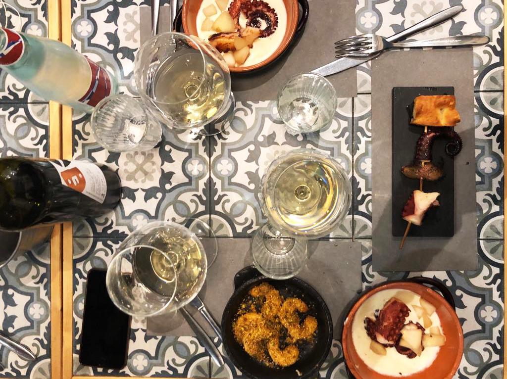 tavolo con piatti di pesce, gamberi, polpop e patate e vino bianco