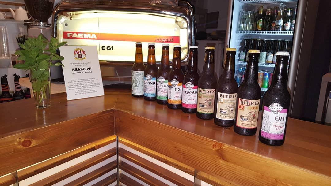 birre artigianali in bottiglia su bancone di legno