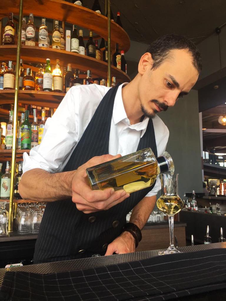 barman che versa distillato nel bicchiere