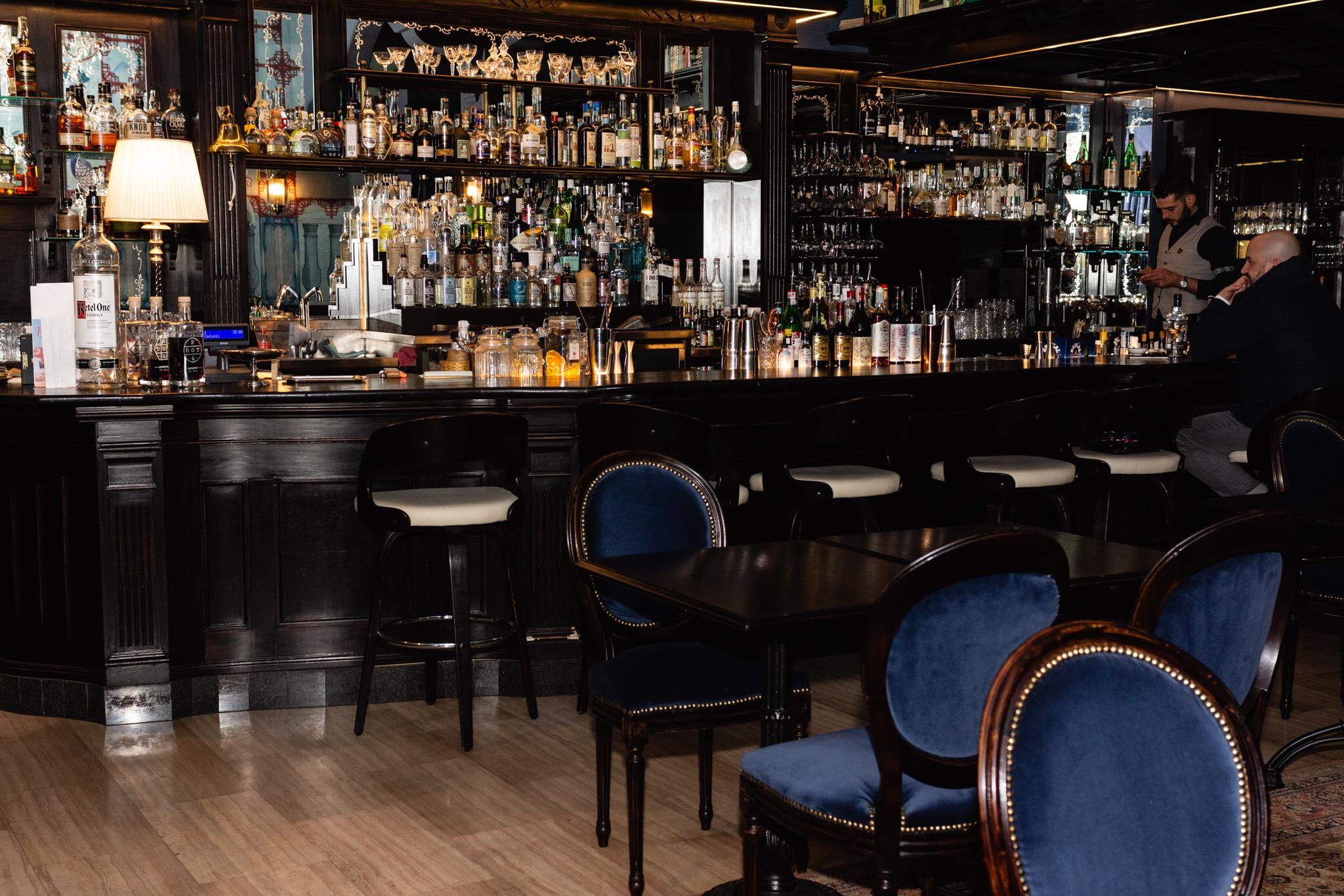 locale con sedie in velluto blu e ricca stagera di distillati premium