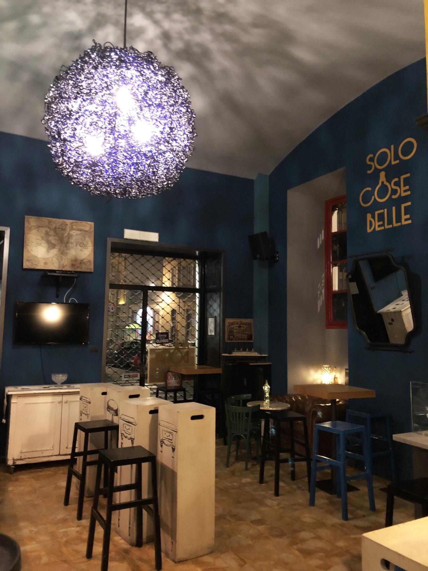 al bona interno locale: pareti blu e sedie e tavolini alti