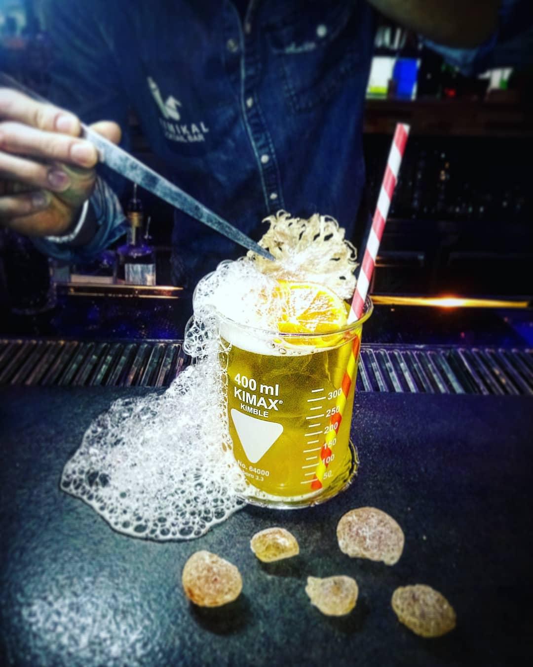 preparazione di un cocktail di colore giallo fatto da un barman chimico