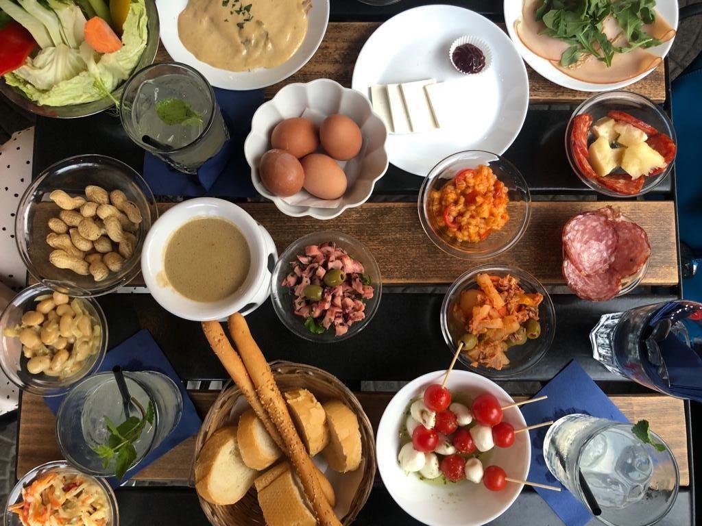 tavolo con piattini per apericena con pomodori e mozzarella, pane, grissini, uova sode, salumi e formaggi, fagioli, bagna cauda