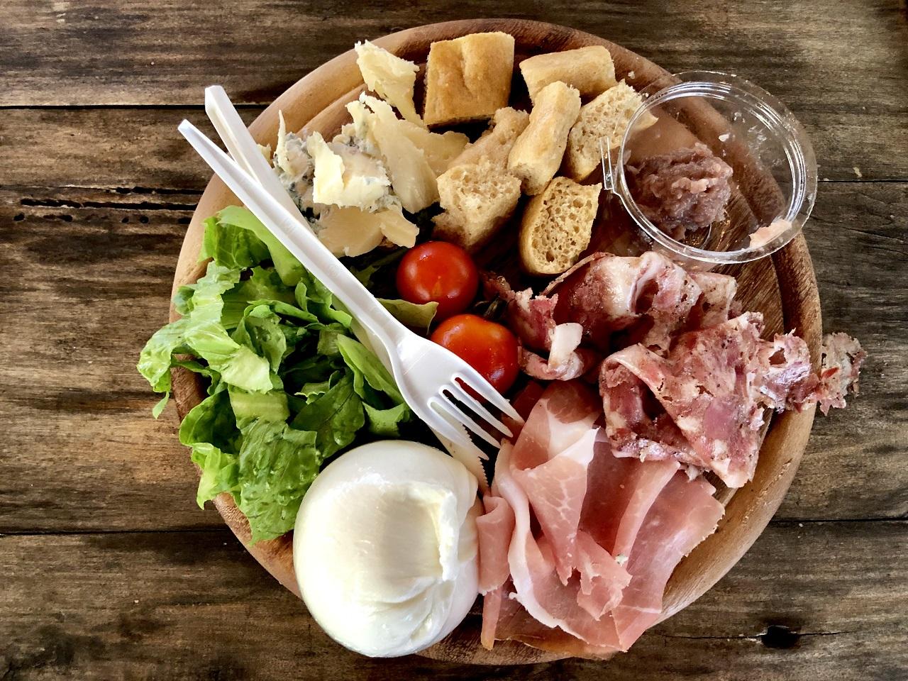tagliere con salumi, formaggi, mozzarella. focaccia, insalata e pomodori