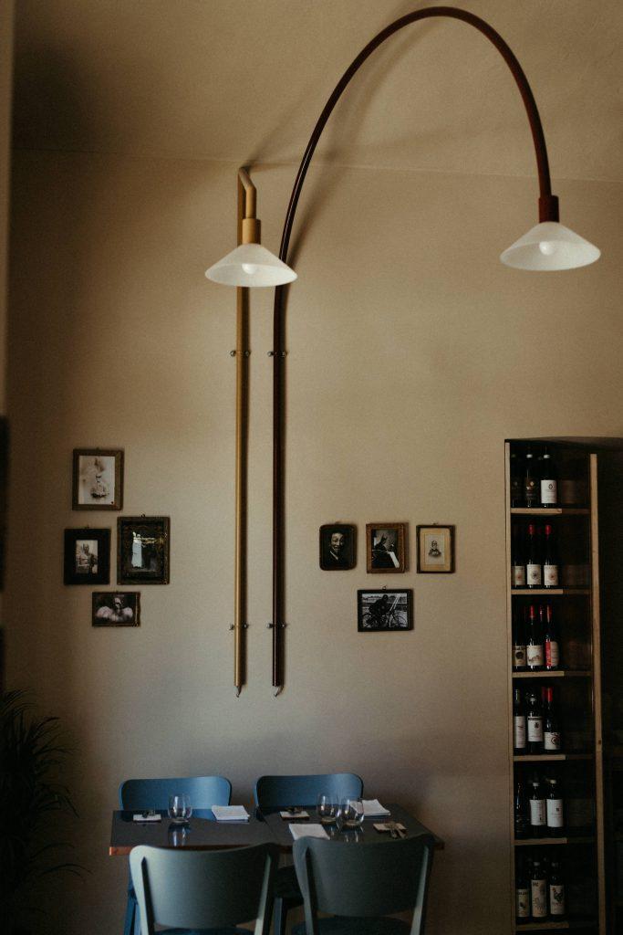 tavolino, sedie, lampada e muro con quadri