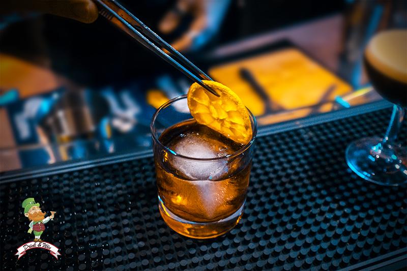 cocktail a cui si sta appoggiando sopra con delle pinzette una fetta di limone