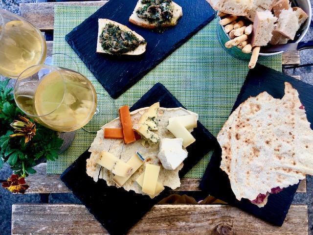 aperitivo con tagliere di formaggi, pane carasau, pane con cime di rapa e 2 calici di vino bianco