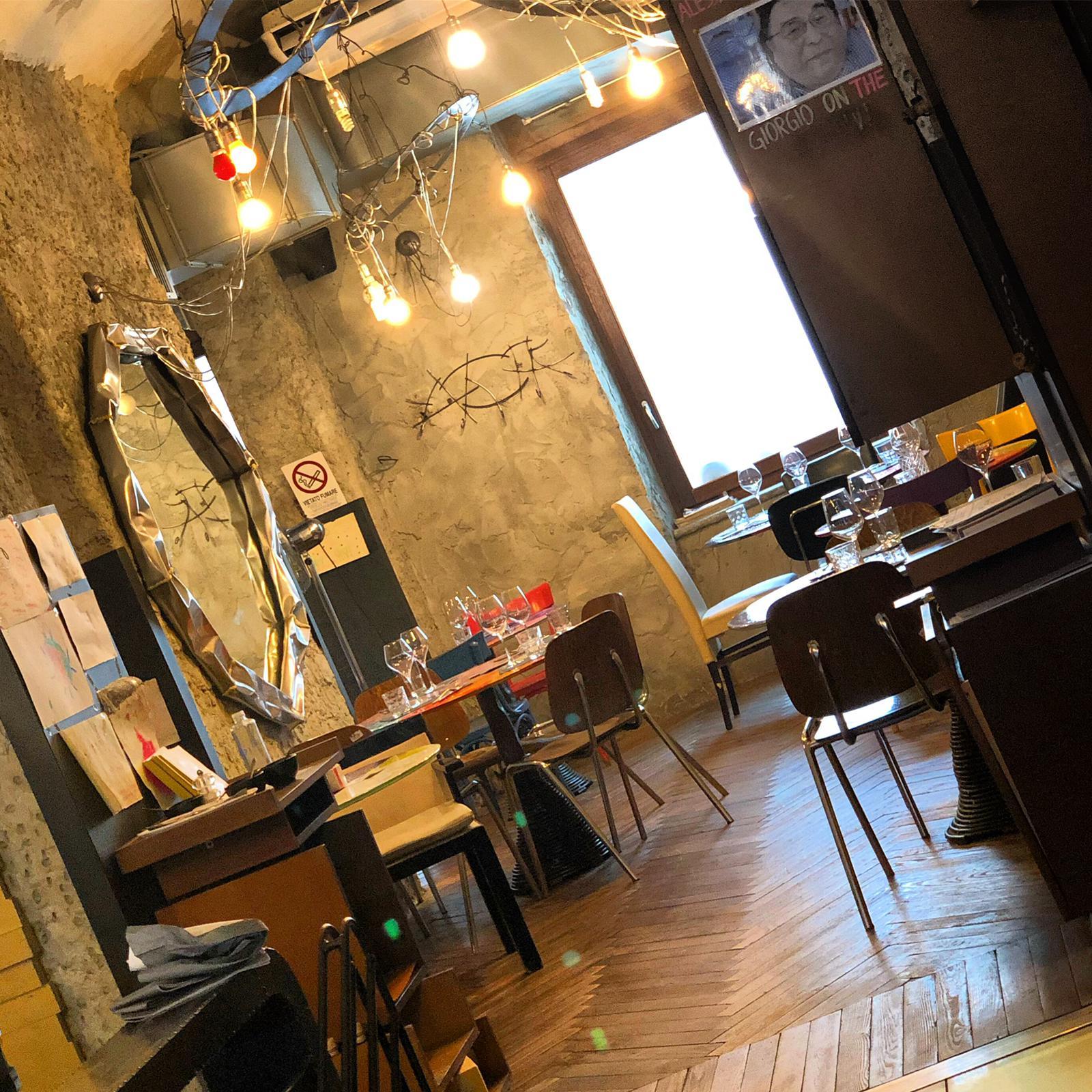 interno locale con sedie e tavolini e specchiio dorato