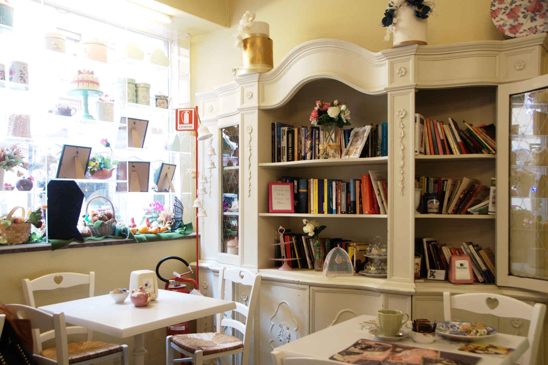 locale con tavolin e sedie bianche e libreria