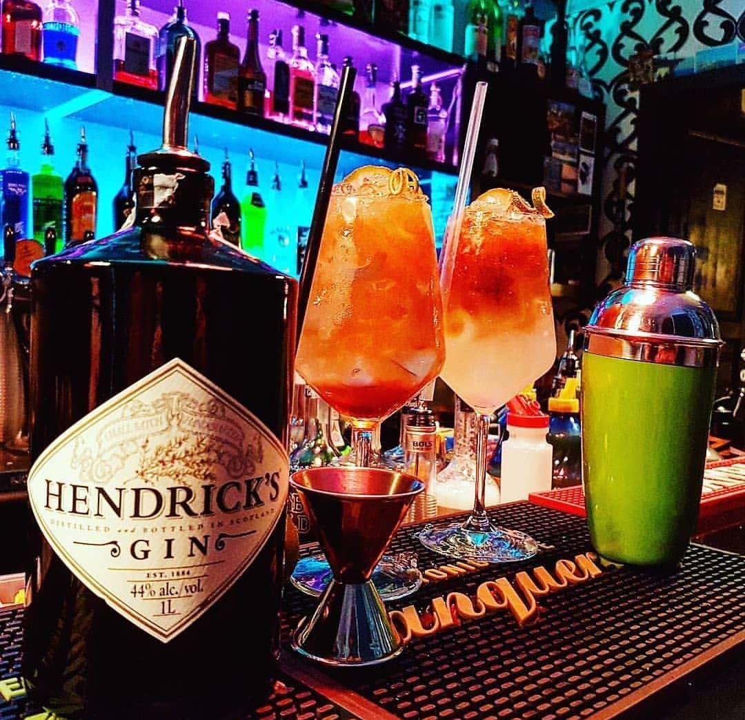 2 cocktail arancioni, uno shaker e bottiglia di gin