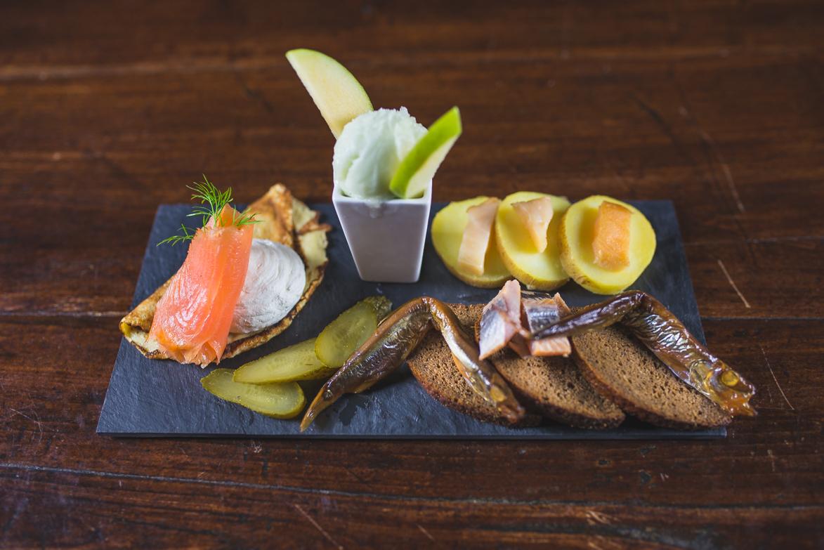 tagliere in pietra con pane, acciughe, salmone affumicato e panna acida