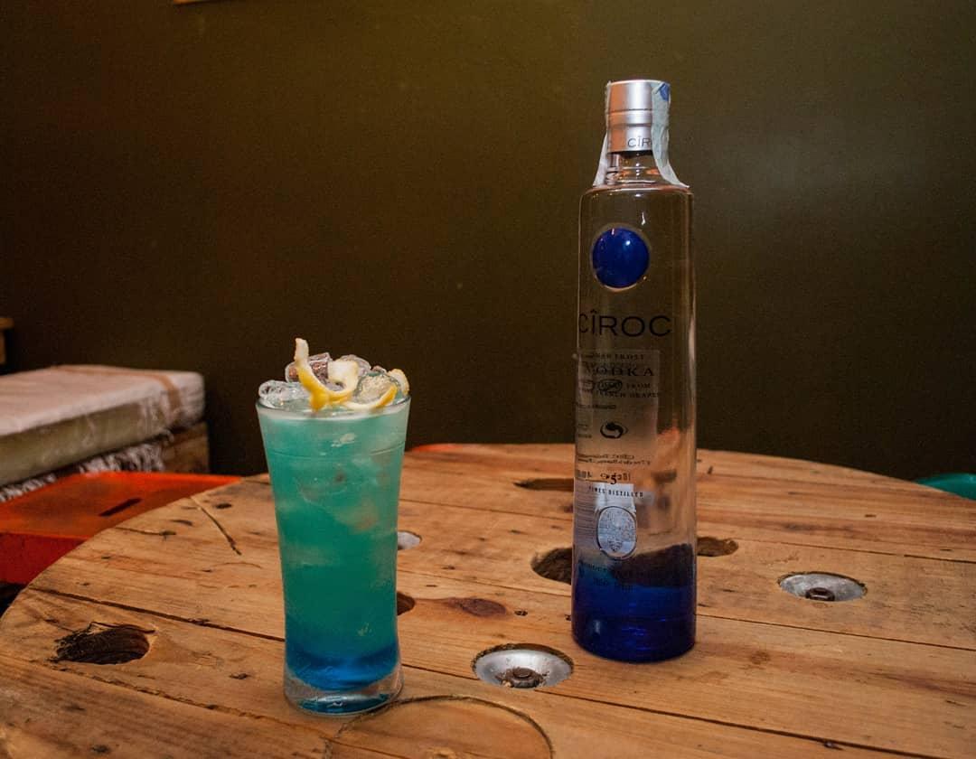 cocktail azzuro e bottiglia di gin