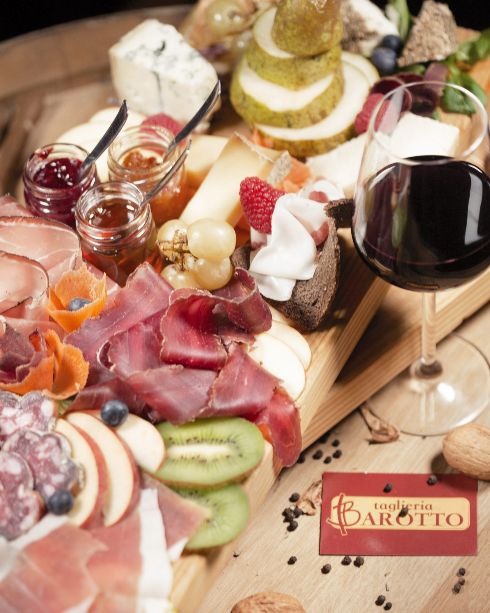 tagliere di salumi, formaggi con frutta e miele ed un bicchiere di vino rosso
