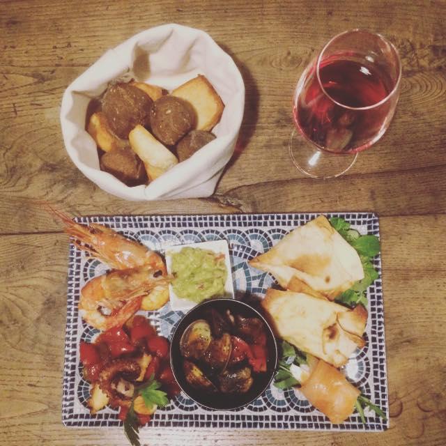 calice di vino rosso, pane, piatto con pesce e orta salata