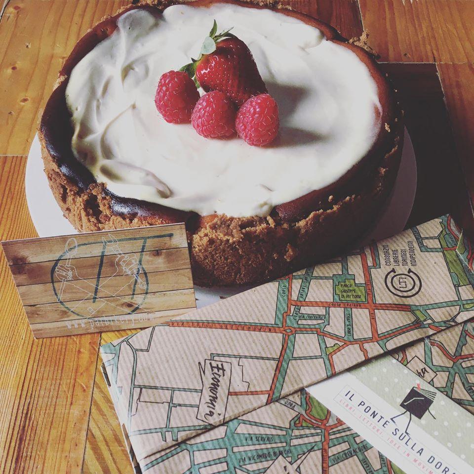 torta con panna e fragole con accanto una mappa