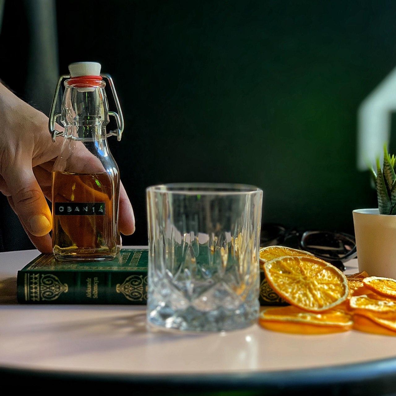 cocktail in bottiglietta sorretta da una mano, bicchiere in vetro, fette di arancia , libro verde