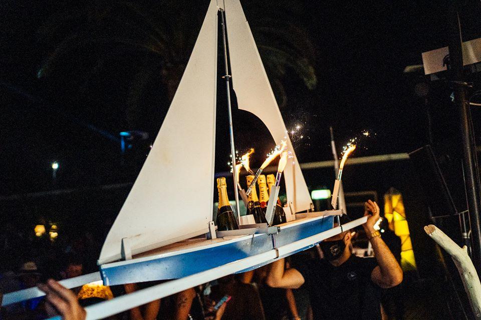 mini barca a vele che fa da vassoio per bottiglie di champagne